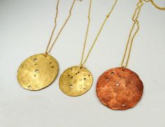 """Wow, brass-based (brass or copper finish) hammered disk with a constellation of choice in holes. Appears to be a 2"""" blank, punched w/ holes or drilled, dapped convex/concave, hammered. Holes are actually irregular like real stars to assuming some dremel action. $42 on etsy from a great shop, make pie not war: http://www.etsy.com/shop/makepienotwar"""