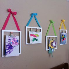 A way to display kids art. I love how the bright ribbon accentuates the kids pictures.