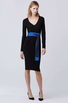 Add instant polish with this structured long sleeve V-neck sheath featuring flattering seam detailing and a bold jewel tone.  It is cut with a back slit for ease of movement and has a zip closure at the back.