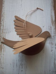 Very bird-like for paper! Each bird is cut from doubled cardstock. Five natural colors-two shades of brown, two of gray and a yellow green. The wings bend any way you like. A paper hanging loop is glued between the wings. Hang with string, ribbon or fishing line to make a mobile or just
