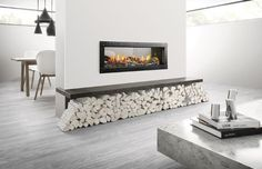 This flush-to-the-wall two-sided see-through design from the Mezzo direct-vent gas fireplace series features a black glass interior and LED illumination of the bed of crushed glass. Named one of Professional Remodeler's 100 Best New Products of 2014. By Heat. #architecture #design #fireplaces