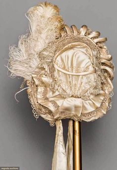 OFF WHITE SILK & LACE BONNET, 1850s Silk satin over tulle covered wire foundation, trimmed w/ Blonde bobbin lace, ostrich plume & self-fabric rouleau bands, tiny red flower bud decoration to brim, China silk lining,- See more at: http://theebonswan.blogspot.com/2014/11/off-white-silk-lace-bonnet-1850s.html?utm_source=feedburner&utm_medium=email&utm_campaign=Feed%3A+InTheSwansShadow+%28In+the+Swan%27s+Shadow%29#sthash.cYGg4pqh.dpuf