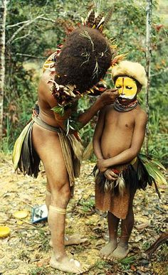 *A Huli man helping a youngster with his face painting.  Papau New Guinea