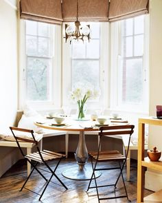 Breakfast nook tucked into bay window with bench seating, a round table with wood top and silver base, wood and iron chairs, gold pendant light and hardwood floors.