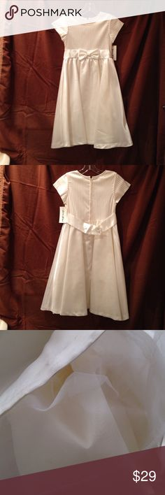 Girls A-line cream satin dress with bow - size 10 Perfect for formal celebrations and holiday. Never used and still with tags. Purchased circa 1996 and never used. With tags. Minimal gray staining at the edge of hem as shown in photo.. Zip closure and back. Lining Under skirt includes tulle and satin for added effect. 25 inches around center band which lays slightly above the navel. 34 inches long shoulder to hem.65% Raime 25% nylon 10% Lycra skirt: 100% polyester. Very good condition…
