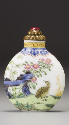 AN IMPERIAL ENAMELLED GLASS 'QUAILS' SNUFF BOTTLE PALACE WORKSHOPS, QING DYNASTY, QIANLONG PERIOD with a flat lip and flat foot, painted in famille-rose enamels with a continuous garden scene featuring three quails on a grassy ground bordered by a convoluted natural rock formation, bamboo, chrysanthemums, asters, one other flowering plant and long grass, the gilt-bronze stopper cast as a formalized chrysanthemum with a ruby finial.