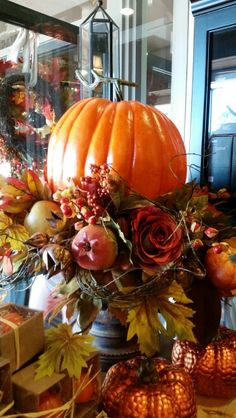 Large pumpkin in a bronze urn. I added angel hair vine to give it a 'spindly' feel. I love the stem.  Designed by Stephanie Alva