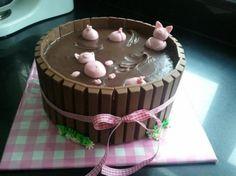 Fin tårta med grisar som badar i gyttja. Roliga tårtor, fina kakor. Rosa marsipangris. Kit-Kat chokladkex på en tårta.