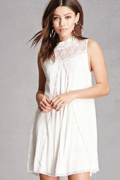 A knit mini dress featuring a sheer illusion lace mock neck, a partial back zipper closure, sleeveless cut, lace paneling throughout, and a trapeze silhouette.  This is an independent brand and not a Forever 21 branded item.