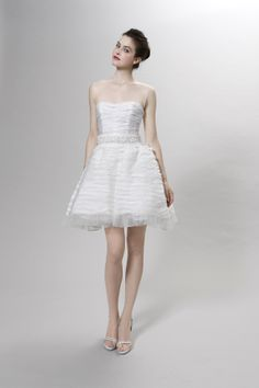 A short dress of pleated organza with an illusion tulle bodice. Floating crystals in the ruffled hem, encrusted flowers on the belt.