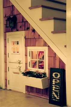 This would likely be the least expensive of the two perhaps because of the overhang?  I really love the divided door and the window and flower box.  How sweet!  Dont feel like you need the stainedc cedar.  Any shingles painted white or an accent color from the room would be cute.  Perhaps a turquoise or a celery green.  I'd be happy to give paint colors and a light fixture.