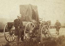 Famed Civil War photographer Alexander Gardner sits beside a traveling darkroom holding a camera lens, Fort Riley, Kansas, 1867. (Library of Congress Prints and Photographs Division)
