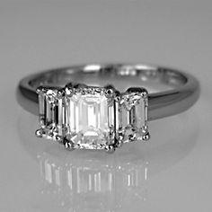 Three stone emerald-cut diamond ring in platinum claw setting