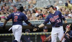AUGUST 12: Justin Morneau #33 of the Minnesota Twins congratulates Denard Span #2 on scoring against the Tampa Bay Rays during the third inning on August 12, 2012 at Target Field in Minneapolis, Minnesota.