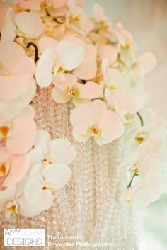 Close up shot of orchids resting on a table chandelier. The crystals and orchids really make a great statement piece. #glamorous @milouandolin