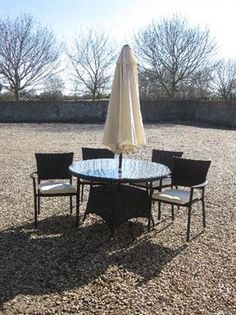 Round cocoa weave garden table 120 dia with four cocoa weave stacking chairs, and cushions, cream parasol and black parasol base