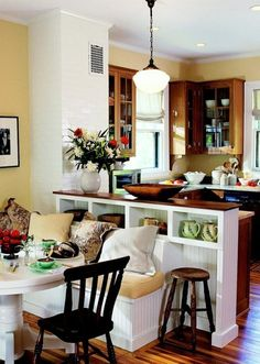 A wall dividing the kitchen and breakfast area was removed, uniting the two spaces and making both brighter and more open. The new eating area features an L-shaped banquette, with storage under the benches and room for additional chairs at the table.    White paint on trim and table lightens the look of an all-wood kitchen.  Wall color of soft yellow picks up the warm undertone of the wood.  The wood top on the white serving counter ties it to the cabinets.