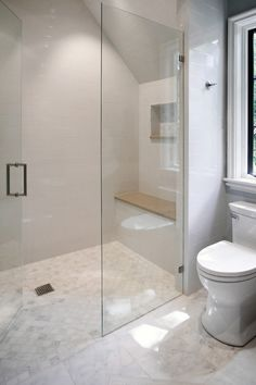 Beautiful attic bathroom features a dormer shower filled with glossy white brick tiles and built in shower bench over honed carrera marble shower floor tiles finished with a seamless glass shower door next to toilet situated under window atop Carrera Bella Marble Tile floor.