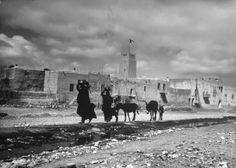 Las mujeres llevan los recipientes de agua en la cabeza, ya que llevan las mulas a lo largo de una carretera en un pueblo del desierto, cerca de Damasco, Siria, 1940.