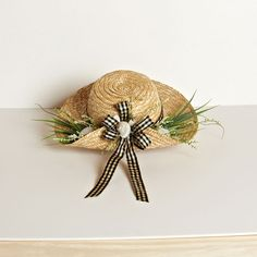 A Natural Straw Hat adorned with decorative ses grasses, heather and seashells and tied with a classic black and cream check bow. From the After Five Collection.