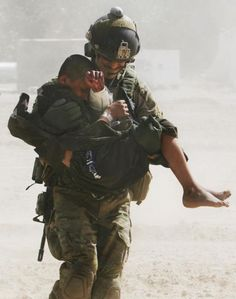 Carrying a wounded Afghan child to the Pave Hawk helicopter in Helmand province, Afghanistan, 2012