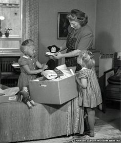 Finland- Maternity Box.  Mother and daughters look at a pack from 1947