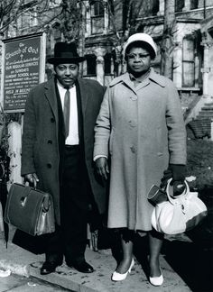 """1960s   """"Pastor F.S. Wallen and his wife outside the Church of God in Effra Road, just off Brixton Town Hall.  It was a small congregation that met in the basement of one of these houses, which are now very grand but back then they were, as you can see, rather run down. It was a hand-clapping tambourine sort of thing. I went to the services to cover them for a story.—it was a very small Caribbean church, it was a culture shock for me.""""--Photographer Val Wilmer."""