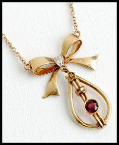 Rose Gold Art Deco lavaliere necklace with garnet, bow, and floral accent.