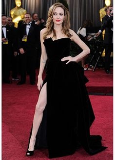 Angelina in an assymetrical strapless gown w/thigh high slit in black velvet by Atelier Versace.  Amazing . . .