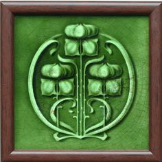 An Art Nouveau low relief deep green ground tile, with a highly stylised triple flower head, stem, and swirled leaf...