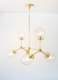 Make a statement with our modern brass chandelier.  This fixture is ideal over kitchen islands or tables and in entryways or stairwells. Perfect for boutiques and shops. Easy to install, this handcrafted chandelier adds style to any space. The chandelier features 6 arms and sockets with 6 clear glass globes. Each globe is 6 inches in diameter. Measures 28 inches long from end to end, with the globes on. (side to side) Shown with a 28 inch hanging length from the ceiling to the bottom of the…