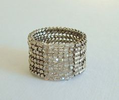 This is a wide band ring woven of Palladium (Silver) Delica Beads and Silver Shade Swarovski Crystals. This ring really makes a statement and could
