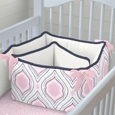 """Crib Bumper in Pink and Navy Moroccan Damask by Carousel Designs.  Our four-sided crib bumpers are produced in one continuous piece and fit standard cribs (using mattresses measuring approximately 28"""" x 52"""") and meet regulation standards with approximately 12"""" long ties and 2-3"""" thick batting, so that you can rest easy. Our crib bumper batting is made from recyclable hypoallergenic polyester fiberfill."""