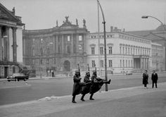 Three East German guards goose-stepping as they march in front of the War Memorial, East Berlin, 1967 by Ralph Crane.