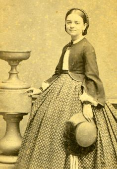 Charming young miss in fashionable skirt, jacket and fine waist combination with decorated hat.