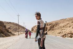 La raza humana en 23 fotos desgarradoras. Una joven yazidí con un fusil de asalto para proteger a su familia contra ISIS.