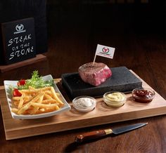 SteakStones Sizzling Steak Set - The set includes a  bamboo board with grooves for three dipping sauces, a ceramic side plate, and of course, most importantly, a hot lava stone that lets you cook your meat or fish right there on the table. The dry heat of the lava stone effectively seals in the moisture and flavor of your favorite protein, whether it's filet, sirloin, ribeye, salmon or tuna, and eliminates the need to use oils or fats when you're cooking.