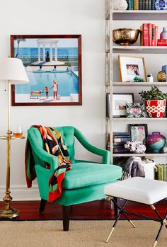 Bright living room nook with a green armchair, graphic art and a bookshelf