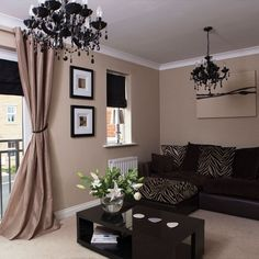 Tan, black, brown living room. Love the long tan drapes and chandeliers. Cozy but sophisticated.