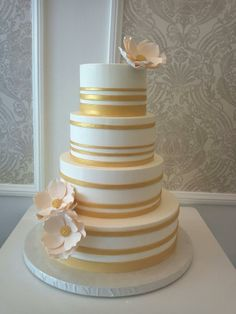 4 tiered wedding cake with Varying Gold Bands and sugar magnolias with sugar brooch centers by Vanilla Bake Shop