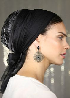 Royal black sinar head covering. The base of this head covering is black spandex. The back of the headcovering is made of lace sewn with textured flowers and sequins. Both ties of this head covering are made of netted black chiffon. The spandex base has