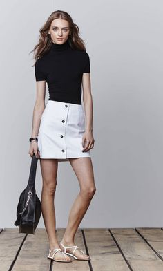 What's black and white and chic all over? This adorable look from MICHAEL Michael Kors. A chic black turtleneck top paired with an of-the-moment A-line skirt and strappy white sandals has breezy summer days written all over it.