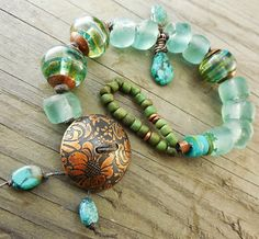 copper button; recycled glass in sea green and rustic olive green Indonesian glass seed beads (Happy Mango); lampwork beads; genuine turquoise.