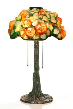 """Magnificent Pairpoint Puffy """"Apple Tree"""" table lamp. The open top shade measuring 8 inches by 16 inches across has butterflies visiting apple blossoms and bumblebees hovering ripened apples. Gold stamped """"Pairpoint Mfg Corp, 1902"""" at the rim's edge. There are a few insignificant touch-up areas inside the lower rim. The tree trunk base has a moss green finish, showing some wear and bears the """"Pairpoint Mfg Co"""", the Pairpoint logo and form number 3092 impressions beneath."""