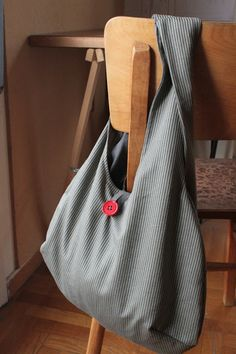 grey bag with red button