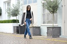 Anisa Sojka styles brown shearling Lindbergh jacket with Monogolian fur cuffs and lining | Black H&M turtle and roll neck top | Blue high-waisted denim mom jeans with a slight flare | Ankle boots with a heel | Round classic Rayban sunglasses | Fashion blogger street style shot in London by David Nyanzi