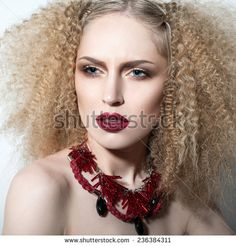 beautiful blond young woman with red lips and big interesting necklace. Evening make-up. Marsala color makeup
