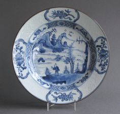 A good quality and unusual Chinese export plate decorated in underglaze blue, and with carved decoration to the rim, dating from the late Kangxi or Yongzheng period c1720-30. The plate is decorated with a central scene of a man standing on a rocky promontory by a lake with a pavilion on the island behind. The rim has a most attractive and unusual decoration of alternating panels of carved floral decoration, and decoration of further precious objects in underglaze blue.