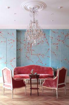 de Gournay: 'Plum Blossom' design in Bleached design colours on Edo ice blue painted silk. George III Parcel Gilt Settle sofa upholstered in Raspberry silk velvet. Tobacco Leaf Vases.