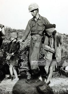 War and Conflict, The Vietnam War, near Loc Son, South Vietnam, pic: January 1966, An American marine escorts a blindfolded and bound pair, a boy and his grandfather, from a village previously held by the Viet Cong